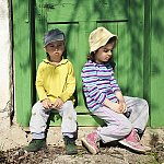 Two children sitting in front of an old door covered in lead-based paint