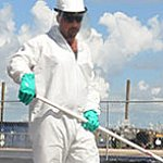 Worker cleaning up oil spill.