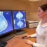 A radiology technician reviews a mammogram.