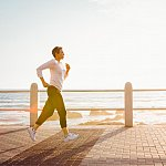 Woman jogging along the oceanfront.