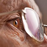 A closeup of a senior woman's eye and glasses