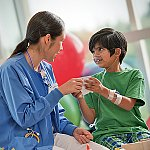 A doctor interacting with a young patient in the hospital