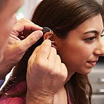 A doctor placing a hearing aid on a patient's ear