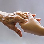 An elderly person's hand holding a young person's hand