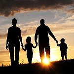 A silhouette of a family holding hands and walking during sunset.