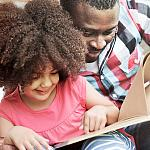 A father and daughter reading together.