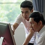 A father and son looking at a computer