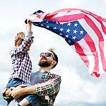 A veteran and his son waving an American flag in the air