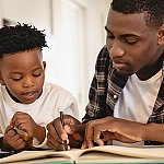 An African American father and son working on an activity book together