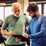 A fitness trainer teaching a senior man exercises to improve balance