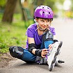 A young girl in rollerblades and protective gear