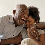 A grandfather and granddaughter laughing together