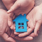 Hands holding a paper cut-out of a house