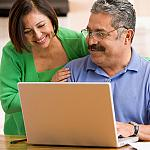 A Hispanic couple looking at their laptop together.