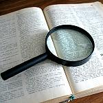 A magnifying glass on top of a book.