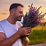 A man smelling a bundle of lavender