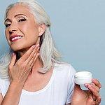 A mature woman moisturizing her neck