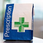 "A paper bag with ""Prescription"" and a green cross on it"