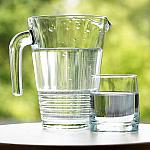 A pitcher and glass of water sitting on a table outside.