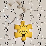 Puzzle pieces with question marks and a light bulb