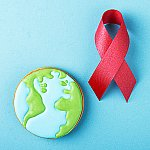 A red awareness ribbon and gingerbread planet earth on a blue background