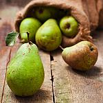 Pears falling out of a straw sack.