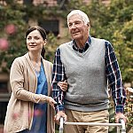 A senior man and caregiver walking outside