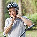 A senior man fastening a bicycle helmet strap