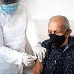 A senior man receiving a vaccine in his arm