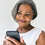 A senior woman using her cell phone for a telehealth call