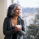 A senior woman drinking tea and looking out a window