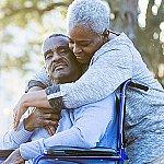 A senior woman embracing a senior man in a wheelchair