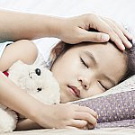 A sick child sleeping while being comforted by a parent
