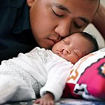 A sleeping baby with a cleft palate being cuddled by her father
