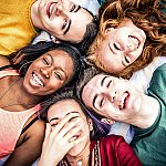 A group of smiling teenagers lying in a circle with their heads touching