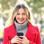 A smiling woman holding a cell phone