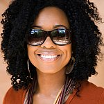 A smiling woman wearing sunglasses.