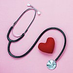 A stethoscope wrapped around a plush red heart