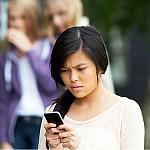 A teenage girl being cyberbullied by peers.