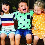 Three multicultural children sitting together