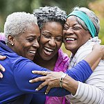 Three women hugging after exercising together