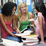 Three young women reading books together in a library