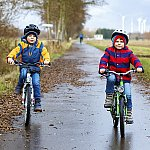 Two young boys riding bicycles on a paved path
