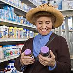 A woman comparing over the counter medicine labels.
