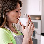 A woman drinking a glass of milk