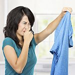 A woman holding a dirty shirt and holding her nose