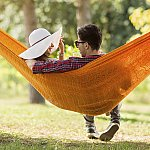 A young couple talking on a hammock