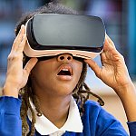 A young girl wearing a virtual reality headset