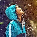 A young woman embracing rainfall