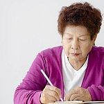 An Asian woman writing.